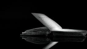 immagine-bianco-e-nero-ad-alto-contrasto-di-vecchio-libro-su-superficie-riflettente-nera-52150930